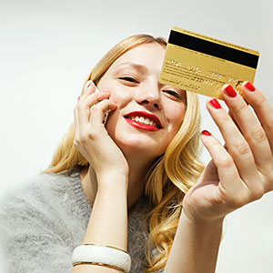 Woman with mobile phone and credit card, smiling copyright Pando Hall, Photographer