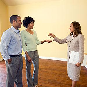Real estate agent giving keys to couple in new home, copyright Mark Scott, Photodisc, Getty Images