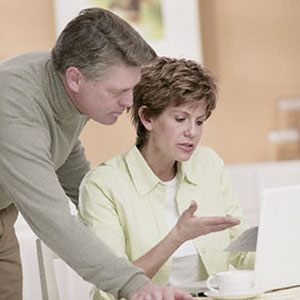 Image: Couple looking at computer - Corbis