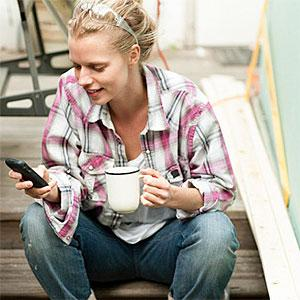 Woman sitting on steps with smartphone copyright Image Source, Image Source, Getty Images