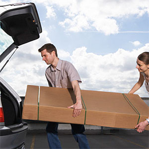 Young man and woman lifting box into car -- Biddiboo, Stockbyte, Getty Images