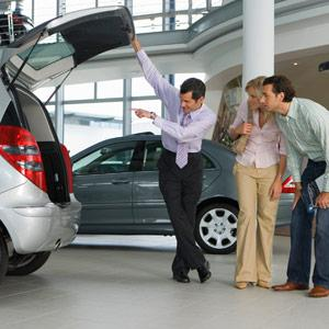 Car salesman showing couple new silver hatchback in car showroom copyright Juice Images, Cultura, Getty Images