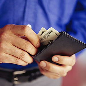 Image: Man Taking Money Out of Wallet -- NULL/Corbis