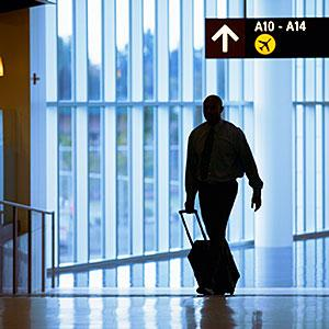 Image: Man pulling suitcase in airport -- Keith Brofsky/UpperCut Images/Getty Images