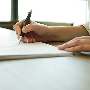 Person signing insurance document copyright Eric Audras, PhotoAlto, Alamy