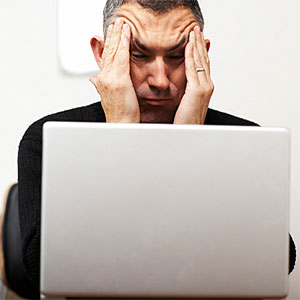 Man making faces from behind laptop James Braund Digital Vision Getty Images