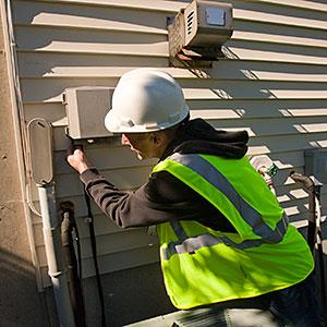 Cable technician installing equipment on the side of a house Huntstock Huntstock Getty Images