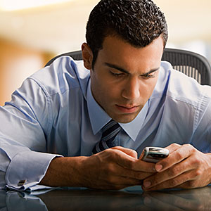 Man using cell phone at desk copyright Jose Luis Pelaez Inc, Blend Images, Getty Images