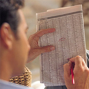 Stocks circled in newspaper Digital Vision Getty Images