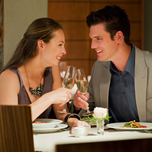 Couple toasting champagne glasses at restaurant table copyright Chris Ryan, OJO Images, Getty Images