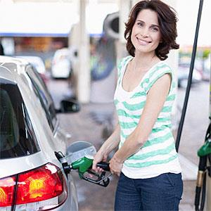 Woman pumping gas into car © Hybrid Images, Cultura, Getty Images