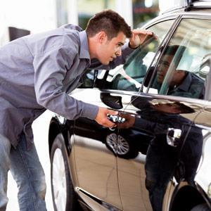 A young man admiring a new car i love images Cultura Getty Images