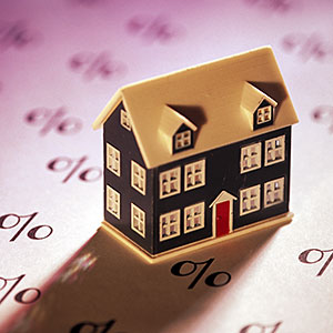 Miniature home on sheet of percent signs copyright Comstock, Getty Images