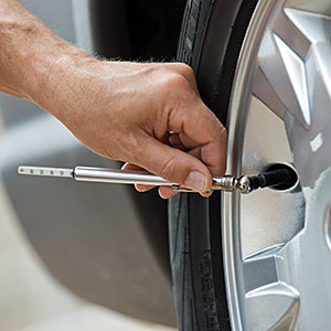  Man checking car tire pressure copyright Tetra Images, Tetra images, Getty Images