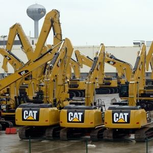 Workers walk past Caterpillar excavator machines at a factory in Gosselies February 28, 2013. Caterpillar, the world's largest maker of construction equipment, plans to cut 1,400 jobs at a plant near Charleroi in Belgium due to high costs and the weak European economy (© Eric Vidal/Reuters)