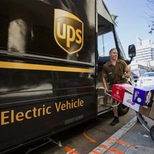 A UPS driver delivers packages from a United Parcel Service (UPS) all-electric vehicle in Sacramento, California, U.S., on Thursday, Feb. 14, 2013