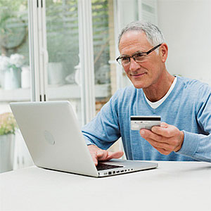 Senior man using laptop with credit card copyright Image Source, Image Source, Getty Images
