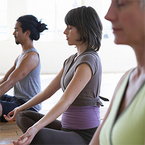 Three adults practicing yoga, focus on young woman with eyes closed, copyright Thomas Northcut, Lifesize, Getty Images