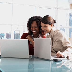 Businesswomen looking at laptops copyright LWA, Larry Williams, Blend Images, Getty Images