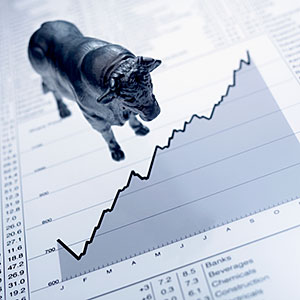 Bull figurine on ascending line graph and list of share prices copyright Adam Gault, OJO Images, Getty Images
