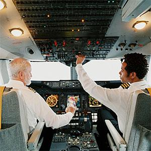 Portrait of Pilots Sitting in the Cockpit, Adjusting the Controls copyright Digital Vision., Digital Vision, Getty Images