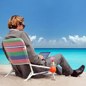 Businessman using tablet PC on beach (© Buena Vista Images/Photodisc/Getty Images)