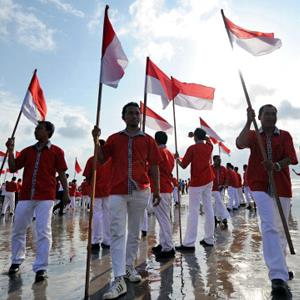 Balinesian people hold Indonesian national flags during a ceremony to celebrate Indonesia's upcoming independence day in Kuta on August 16, 2011