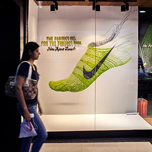 A pedestrian walks past a Nike Inc. in New Delhi, India on June 9, 2013 (© Prashanth Vishwanathan/Bloomberg via Getty Images)