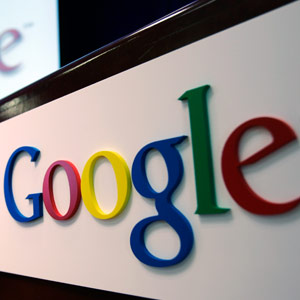 The Google logo is seen on a podium and projected on a screen at Google headquarters in Mountain View, Califorina Paul Sakuma/AP