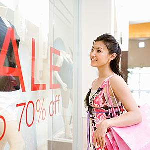 Woman looking at mannequins in boutique, smiling (c) Michael Hitoshi/Digital Vision/Getty Images