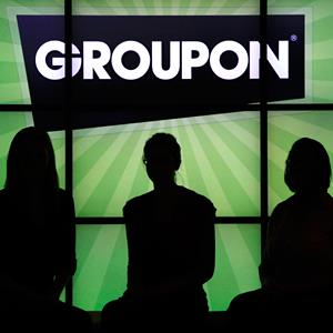 Groupon employees stand in front of the company logo at the company's Chicago office, on Sept. 22, 2011 (© Charles Rex Arbogast/AP)