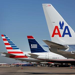 A US Airways airplane sits between two American Airlines jets at Dallas Fort Worth Airport, on February 14, 2013 (© Mike Fuentes/Bloomberg via Getty Images)