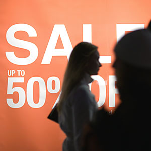 Poster proclaiming Sale up to 50% off and shoppers silhouetted in foreground copyright Michele Constantin, PhotoAlto Agency RF, Getty Images