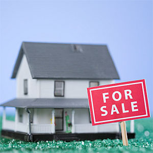 For Sale sign board in front of a model home © Glow Images, Glowimages, Getty Images