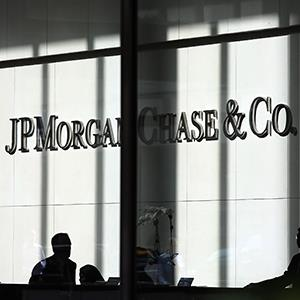 People pass a sign for JPMorgan Chase & Co. at headquarters in Manhattan in New York City (© Spencer Platt/Getty Images)