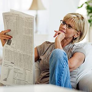 Woman reading newspaper in livingroom © Tetra images/Getty Images