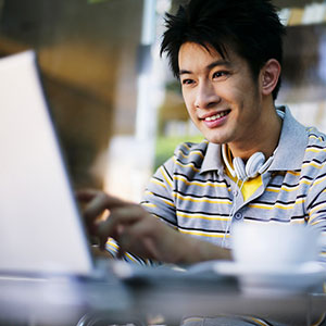 Man with laptop (© Ken Seet/SuperStock)