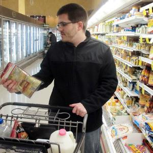 Ben Rellinger selects shredded cheese and milk at a Milwaukee grocery store. © Dinesh Ramde/AP