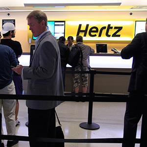 Customers waiting in line at a Hertz rental car counter at San Jose International Airport in San Jose, Calif. © Paul Sakuma/AP