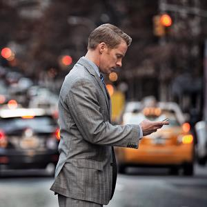 Businessman using cell phone near busy street (© Mint Images - Tim Pannell/Photodisc/Getty Images)