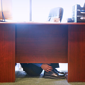 Businessman sitting beneath desk, side view (Corbis)
