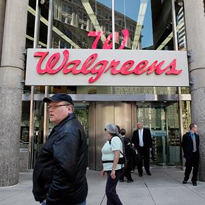 People walk by a Walgreens in Boston, Mass., on April 30, 2013 (Photo by Wendy Maeda/The Boston Globe via Getty Images)