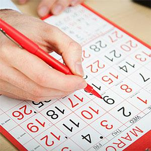 Office worker marking calendar with red pen © Image Source, Image Source, Getty Images