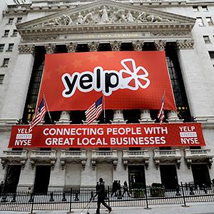 Caption: A view of a Yelp sign on the front of the New York Stock Exchange in 2012