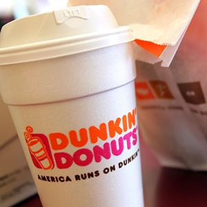 A cup of Dunkin' Donuts coffee and a donut bag (© Tim Boyle/Getty Images)