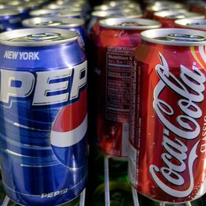 Cans of Pepsi and Coke on display © Mark Lennihan/AP