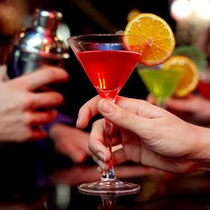 Woman holding martini cocktail at a bar (© mediaphotos/E+/Getty Images)License: RF