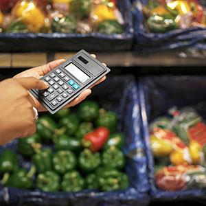 Close-up of a person using a calculator in a supermarket (© George Doyle/Stockbyte/Getty Images)