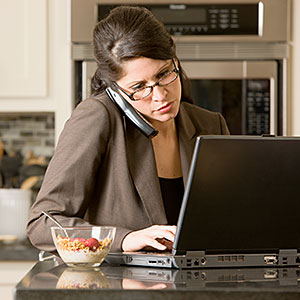Businesswoman using laptop and telephone &#169; Terry Vine, Blend Images, Getty Images