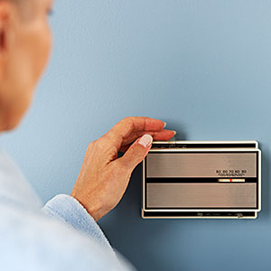 Logo: Woman Adjusting Thermostat (Fuse, Getty Images)